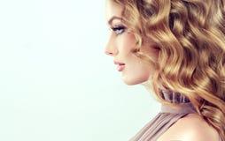 有中间长度,密集和卷发的可爱的妇女金发碧眼的女人 库存图片