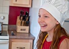 有主厨的帽子的十岁的愉快的女孩 免版税库存照片