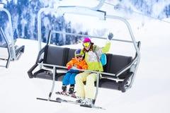 有举在滑雪电缆车的男孩的母亲 免版税库存图片