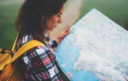 有举行在手上和看在地图有雾的山,背景的旅游旅客远足者西班牙的背包的行家女孩  免版税图库摄影