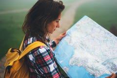 有举行在手上和看在地图有雾的山,背景的旅游旅客远足者西班牙的背包的行家女孩  免版税库存图片