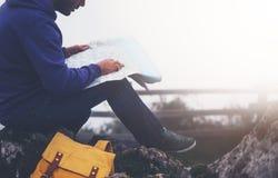 有举行在手上和看在地图有雾的山,背景的旅游旅客远足者西班牙的背包的行家年轻人  库存图片