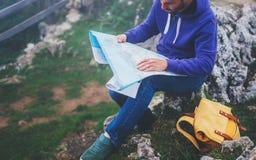 有举行在手上和看在地图有雾的山,背景的旅游旅客远足者西班牙的背包的行家年轻人  免版税库存图片
