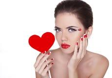 有举行红色心脏iso的魅力明亮的构成的美丽的妇女 免版税库存图片