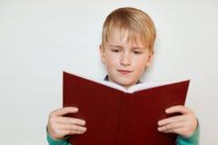 有举行红色的金发和蓝眼睛的一个小俏丽的男孩打开了书读的有趣的故事 七岁男孩读书 免版税库存照片
