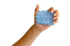 有举行蓝色冬天销售的银色指甲盖的妇女的手 免版税库存图片