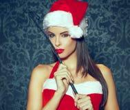 有举行鞭子户内por的红色嘴唇的性感的浅黑肤色的男人圣诞老人妇女 免版税库存图片