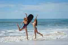 有举行bodyboards的适合身体的健康运动冲浪者女朋友 库存图片