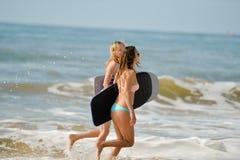 有举行bodyboards的适合身体的健康运动冲浪者女朋友 库存照片