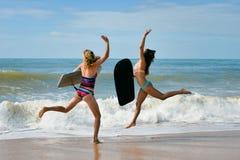 有举行bodyboards的适合身体的健康运动冲浪者女朋友 图库摄影
