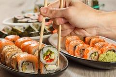 有举行Hosomaki的两双筷子的男性手滚动与vegeta 免版税图库摄影