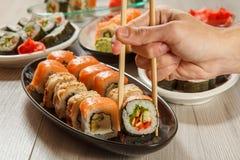 有举行Hosomaki的两双筷子的男性手滚动与vegeta 库存图片