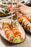 有举行Hosomaki的两双筷子的男性手滚动与vegeta 库存照片
