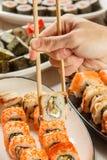 有举行Uramaki的两双筷子的男性手滚动与海鳗之类, 免版税库存照片