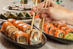 有举行Uramaki的两双筷子的男性手滚动与海鳗之类 免版税库存图片