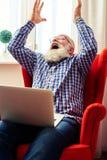 有举他的手的膝上型计算机的愉快的老人  库存照片