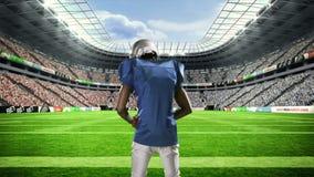 有举他的胳膊的球的美国橄榄球运动员 影视素材