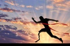 有义肢横穿终点线的日落残疾paralympic赛跑者 免版税库存图片
