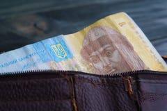有乌克兰hrivna票据的老破旧的皮革钱包在木t 免版税库存照片