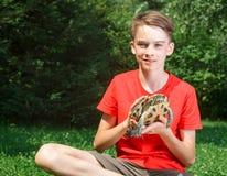有乌龟室外焦点的青少年的男孩在乌龟 图库摄影