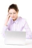 有乏味神色的疲乏的少妇在膝上型计算机前面 库存照片