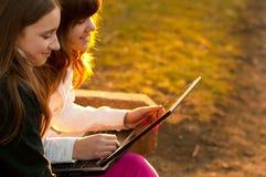 有乐趣的女孩少年的笔记本 免版税库存照片
