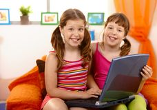 有乐趣的女孩膝上型计算机 库存照片