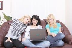 有乐趣的女朋友互联网冲浪 免版税库存照片