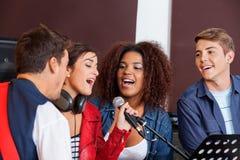 有乐队成员的歌手在录音室 免版税图库摄影