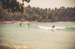有乘坐冲浪板的年轻冲浪者的海洋在美丽的海湾的波浪 库存图片