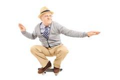 有乘坐滑板的帽子的老人 库存照片