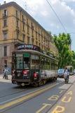有乘客的减速火箭的黑电车在街道上在米兰,意大利 免版税图库摄影