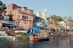 有乘客的河船漂浮在河下 免版税库存照片