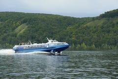 有乘客的蓝色小船在一条河的一架滑翔机的后面的 库存照片