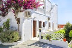 有九重葛的传统希腊房子在锡拉,圣托里尼,希腊开花 免版税库存照片