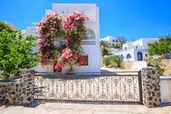 有九重葛的传统希腊房子在锡拉,圣托里尼,希腊开花 图库摄影