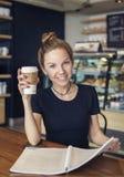有习字簿的妇女和一杯咖啡 免版税库存照片