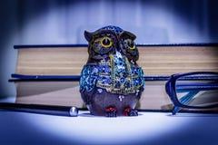 有书、笔和玻璃的逗人喜爱的猫头鹰小雕象 免版税库存照片