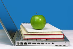 有书、笔记本和绿色苹果的膝上型计算机 免版税库存照片