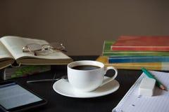 有书、镜片、智能手机和咖啡的工作场所 免版税图库摄影