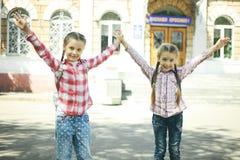 有书包的两位快乐的女小学生 库存图片