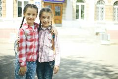有书包的两位快乐的女小学生 免版税图库摄影