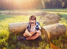 有书包阅读书的男孩在瑜伽姿势 免版税库存照片