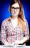 戴书呆子眼镜的努力地学会镇静的少妇 图库摄影