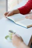 有书和一杯咖啡的两个人 库存图片