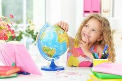 有书和地球的逗人喜爱的学生女孩 库存图片