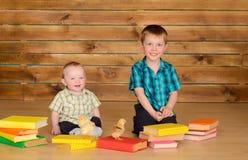 有书和小鸡的更老和更加年轻的男孩 库存照片