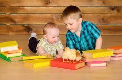有书和小鸡的更老和更加年轻的男孩 图库摄影