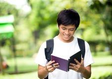 有书和微笑的年轻英俊的亚裔学生在室外 库存图片