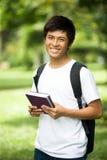 有书和微笑的年轻英俊的亚裔学生在室外 免版税库存图片
